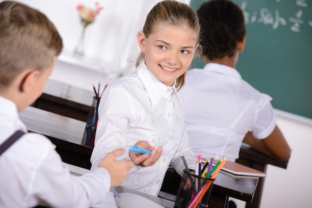 女の子がクラスの男の子とペンを共有します。