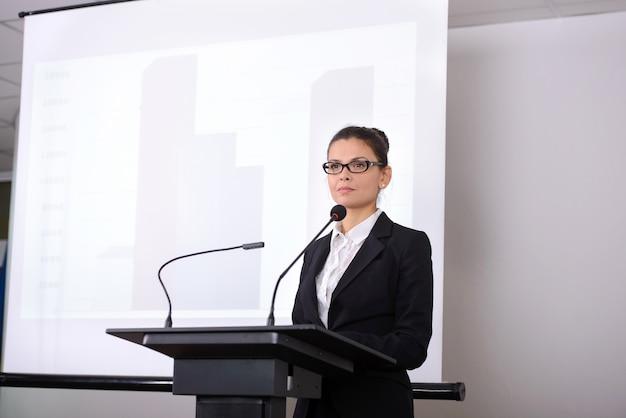ビジネス会議の掲示板の近くの女性スピーカー。