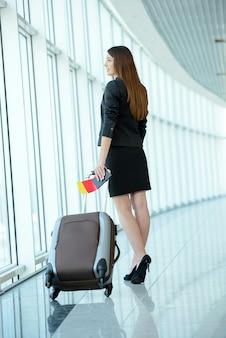 Молодая женщина, потянув багаж в аэропорту.