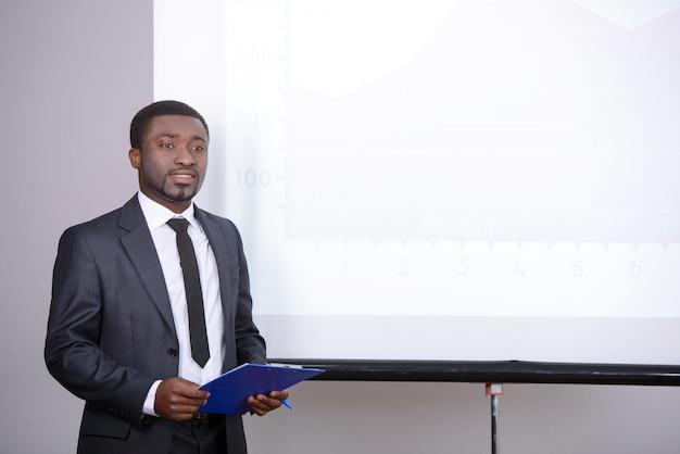 男がボードの近くに立ち、プレゼンテーションを見せる。