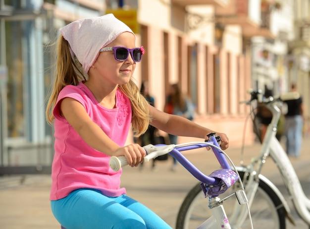 街の通りに自転車に乗って笑顔の女の子。
