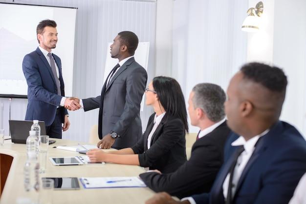 Мужчины пожимают друг другу руки на совещании в офисе.