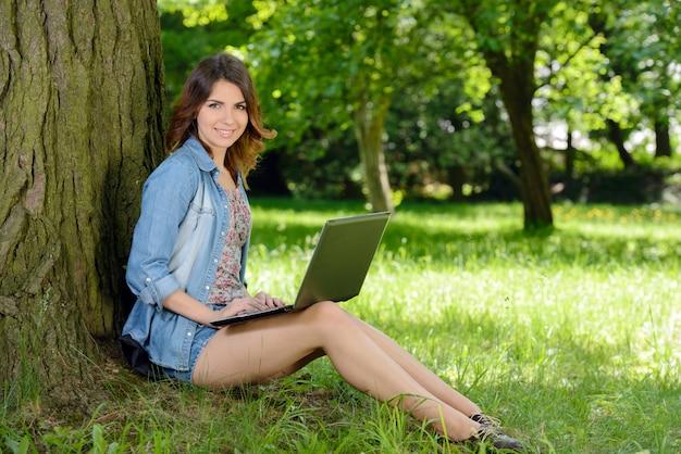 Улыбается подросток с ноутбуком на природе.