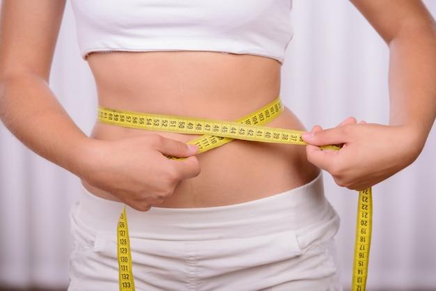 フィットネス女性彼女の腰の測定