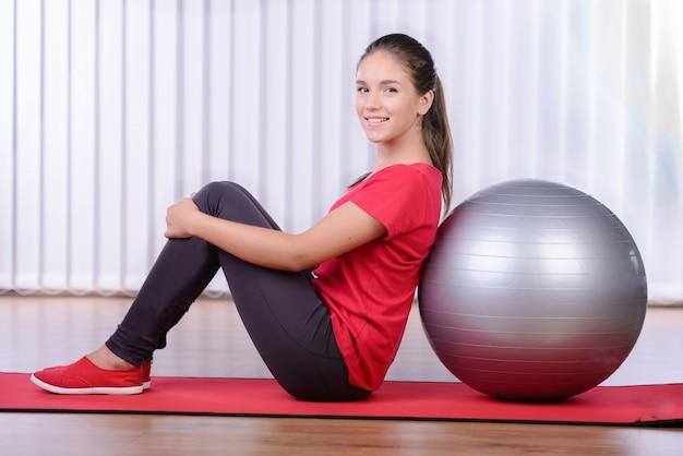 Девушка сидит на коврике рядом с мячом для фитнеса.
