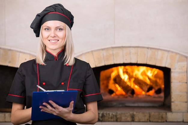 Прикольная женщина, повар-пекарь в черной униформе.
