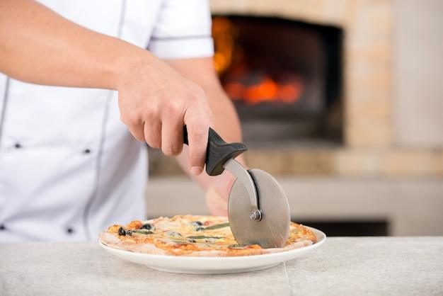 ハンドシェフは、キッチンでピザを準備しています。