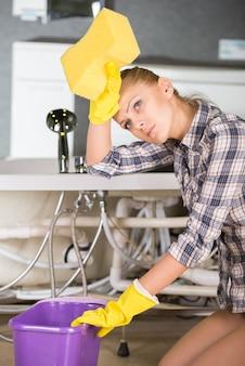 浴室の床を掃除しながら女性。
