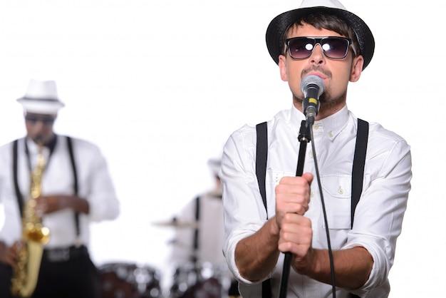 メガネと帽子を持つ男がマイクのそばに立ち歌う。