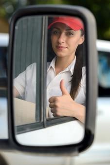 Девушка сидит за рулем и показывает палец вверх.