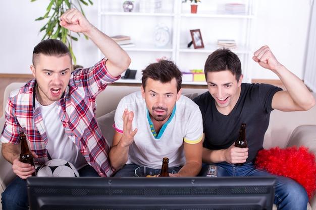Три спортивных болельщика смотрят игру по телевизору дома.
