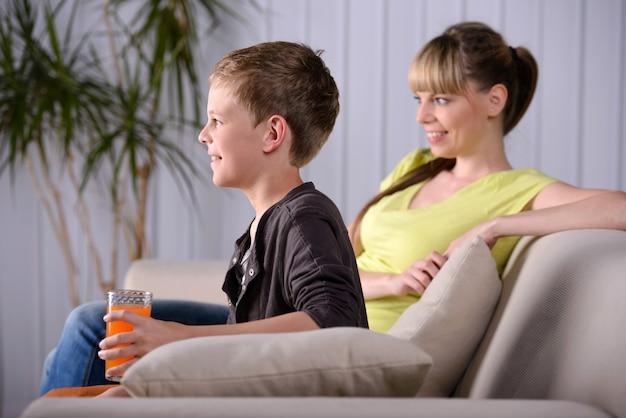 テレビを見ている彼女の若い息子を持つ若い母親。