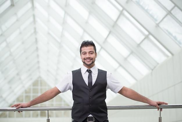 Бизнесмен стоя на офисе и улыбке.