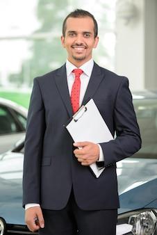 車のセールスマンがディーラーに立っていると車を指しています。