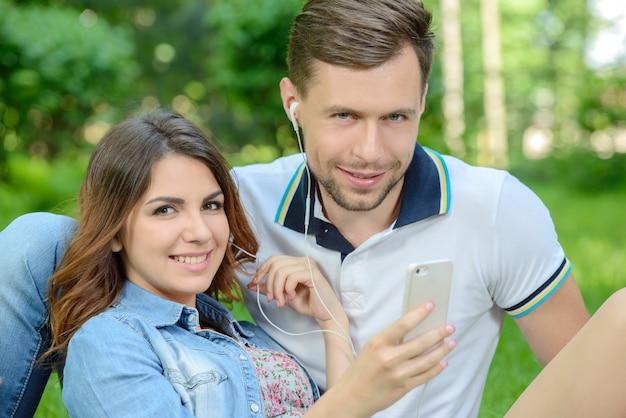 愛する若いカップルが音楽を聴きます。