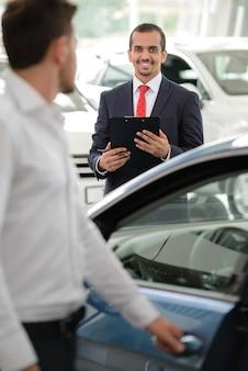 Продавец стоит в автосалоне и помогает клиенту.