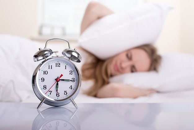 Молодая женщина с будильником на кровати на утро.