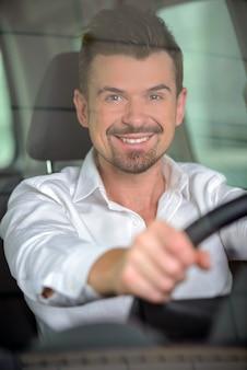 自信がある実業家は車の中で座っています。