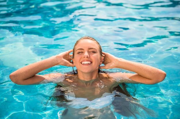 Молодая красивая женщина отдыхает в бассейне.