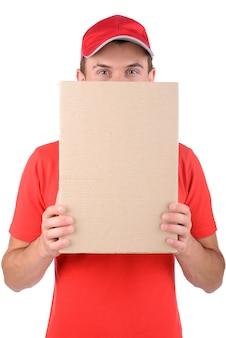 Счастливый улыбающийся доставщик скрыть лицо за коробкой.