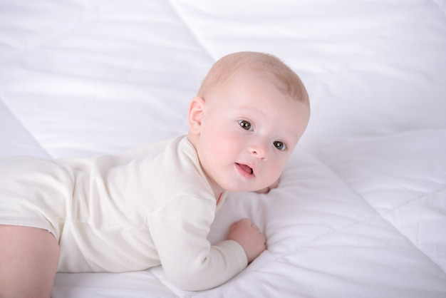 小さな赤ちゃんは白いベッドの上をクロールします。