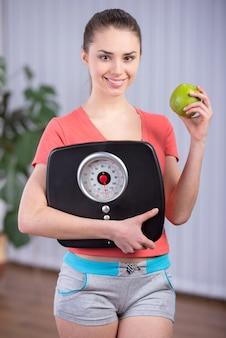 減量のためのスケールとアップルの食事を食べる女性。