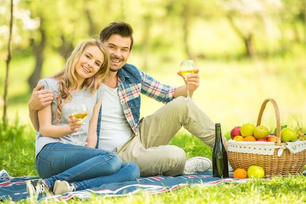 美しいカップルは、ピクニックを持つカジュアルな服を着てください。