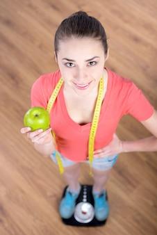 体重の上に立っている若い美しいフィットネス女の子。