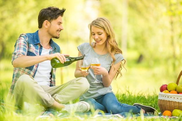 公園でピクニックを持っているとワインを飲む若いカップル。