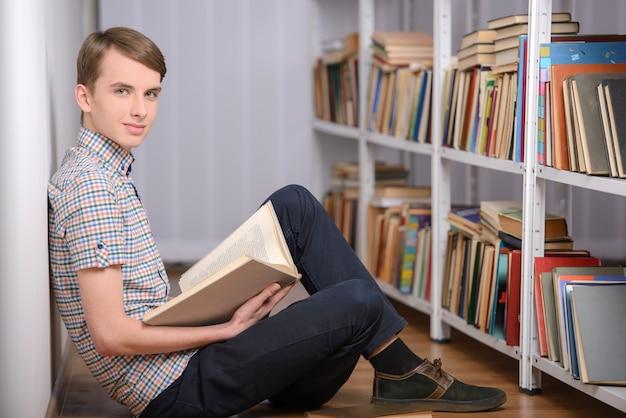 開いた本を持つ賢い人が読んでいます。