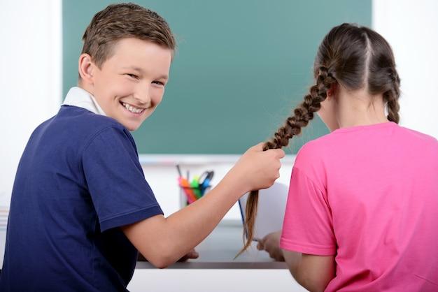 少年は教室でピグテールのために少女を引っ張る。