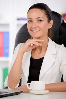 自信を持っている中年の実業家が仕事に座っています。