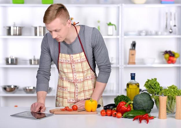 若い男が自宅でサラダを準備します。