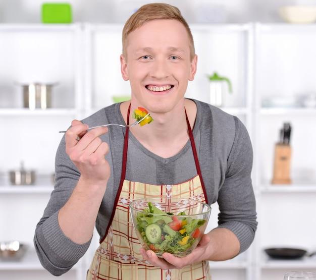 ハンサムな男は台所でサラダを試飲します。