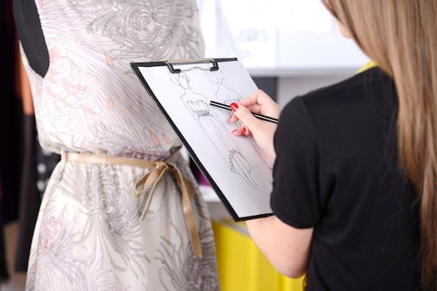 女の子はスタジオで紙の上のドレスをスケッチします。