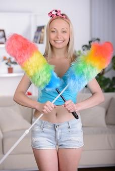 Красивая домохозяйка с уборкой подметает дома.