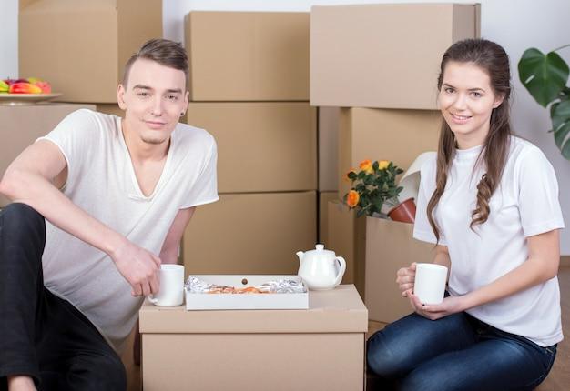 Пары лежа совместно между стогами картонной коробки.