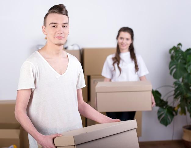 Девушка и мужчина несут коробки в новой квартире.