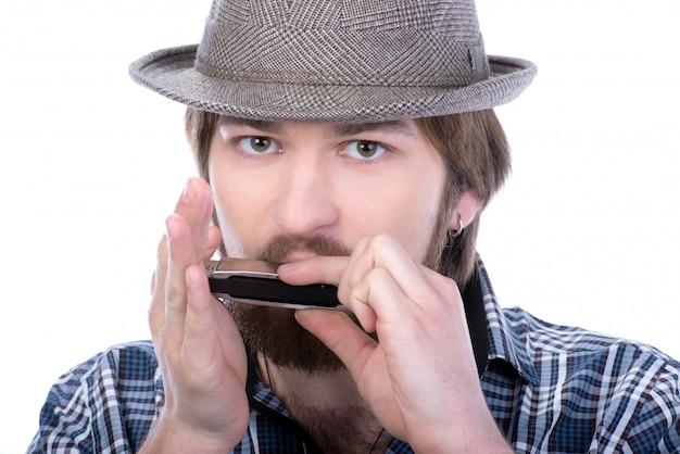 Человек играет на губной гармошке