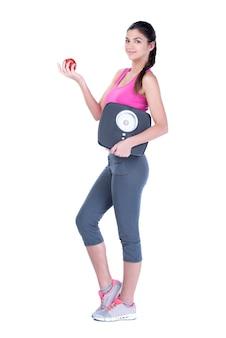 スケールとアップルの健康的な食事を食べる女性。