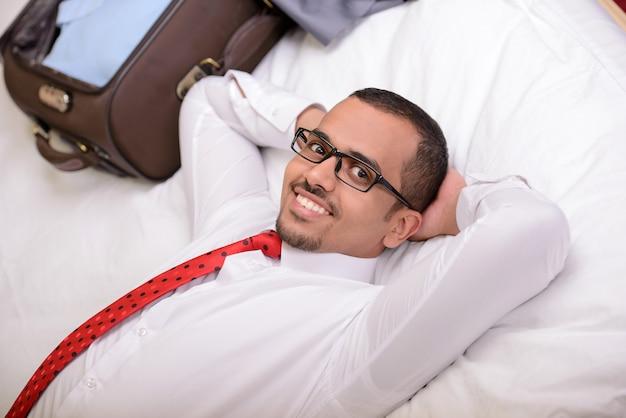 ホテルのベッドに横になっているスーツケースを持ったビジネスマン。