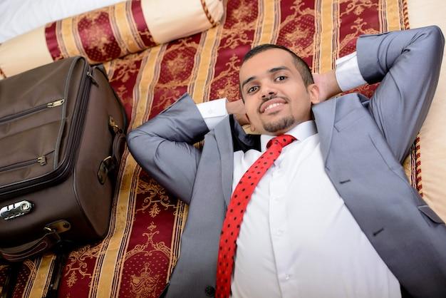 ベッドに横になっているスーツケースを持ったビジネスマン。