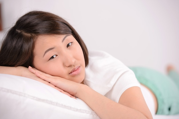 Азиатская женщина, курорты, лежа в постели