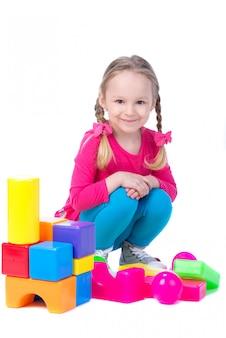 子供は色のおもちゃのブロックから家を建てています。