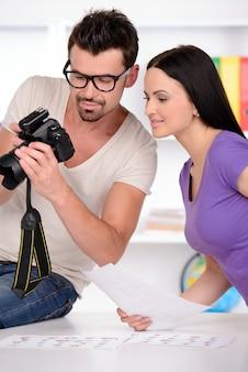 写真家はカメラで写真を見ています。
