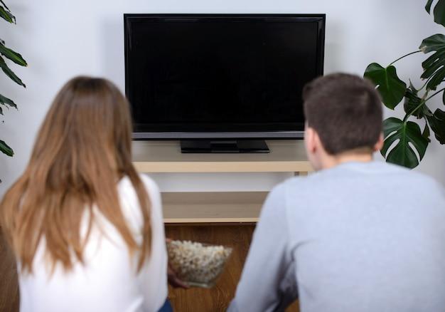 一緒にテレビを見てリラックスした若いカップル。