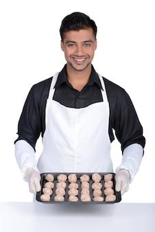 Профессиональный шеф-повар показывает еду на тарелку и улыбается.