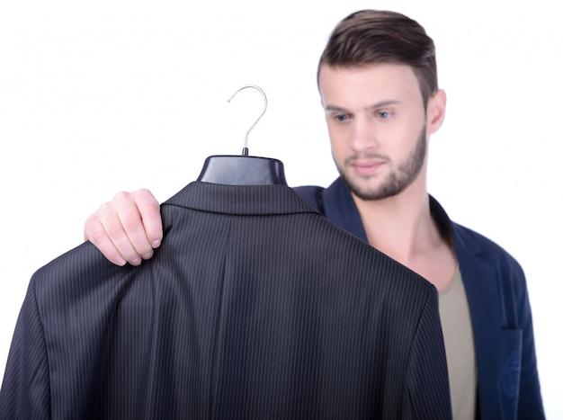若い男が買い物にスーツのジャケットを選択します。