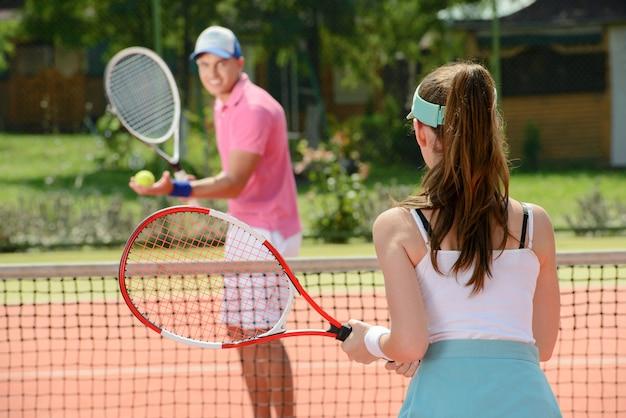 Мужчина и девушка вместе играют в теннис на улице.