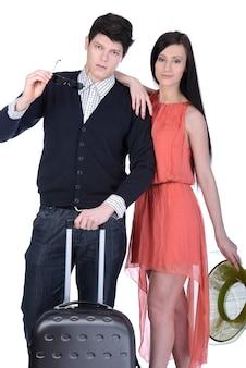 旅行スーツケースを持って歩く若いカップル。
